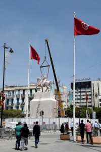 A picture taken on May 23, 2016 shows people walk past the statue of Tunisia's first president, Habib Bourguiba, on a horse from La Goulette, upon relocating it back to its original location in central Tunis.  / AFP / FETHI BELAID