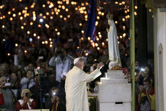 pope-francis-touches-the-statue-of-our-lady-of-fatima-in-the-chapel-of-the-apparitions-at-the-shrine-of-our-lady-of-fatima-during-the-blessing-of-the-candles-ceremony-in-portugal_5878553